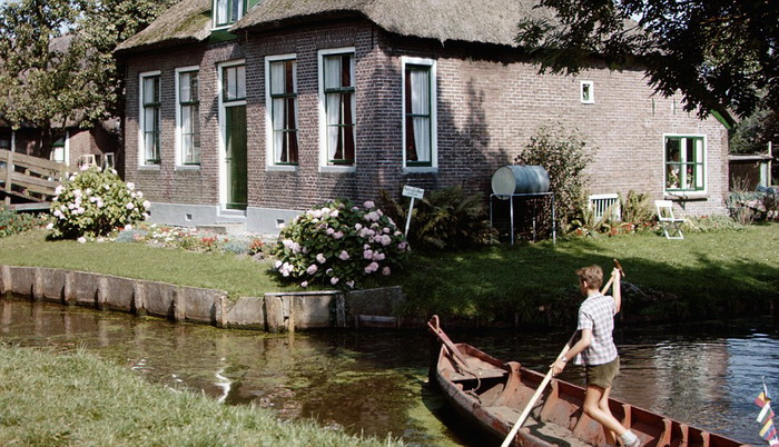 ca. 1950-1980, Giethoorn, Netherlands --- A boy poles a punt through a canal in Giethoorn, Netherlands, a village entirely surrounded by canals. --- Image by © Paul Almasy/CORBIS