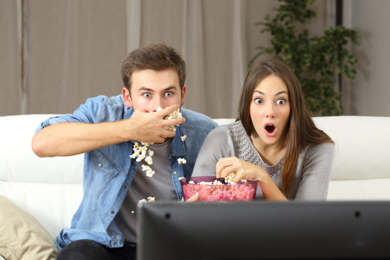 couple eating in front of tv