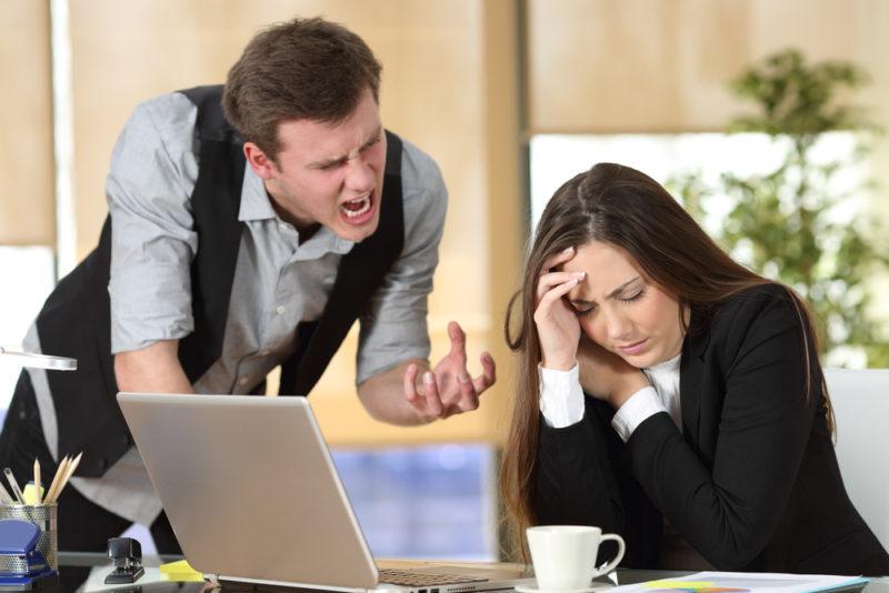 man yelling at woman desk